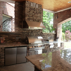Outdoor kitchen with stainless steel grill and granite countertops