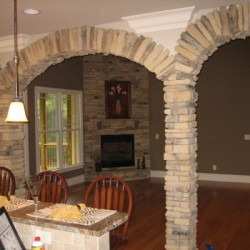 Custom home, kitchen, counter eating area, custom stone arches to family room