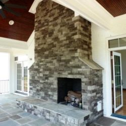 Screened in porch with large stone fireplace